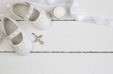 Christening background with white baby booties, crystal cross and satin ribbon isolated on white plank floor