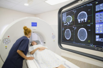 Radiographer talking to a patient in CT scan room