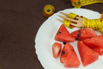 Dietary concept. Melon on a wooden table. Strict diet. Overweight reduction.