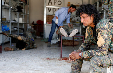 A Syrian Democratic Forces (SDF) fighter sit as medics treat his comrades injured by sniper fired by Islamic State militants in a field hospital in Raqqa