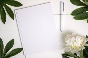 Blank white book, journal, wedding guestbook, notebook mockup. Object for design and branding. White peony and wooden texture, top view.