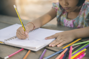 Adorable little girl doing homework,bored or tired asian kid writing on paper.Little Child hate doing homework,stress child for exam,colored pencils on wooden desk