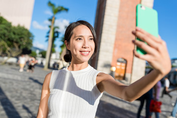 Young woman taking selfie with mobile phone in Hong Kong
