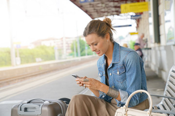 Young woman using smartphone while waiting for the train