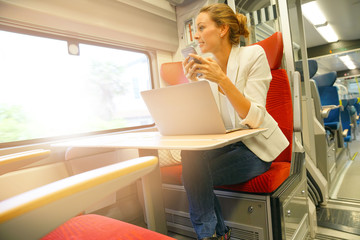 Businesswoman in train working on laptop and talking on phone