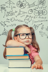 beautiful cute little genius girl with books. Math formulas, problems over her head
