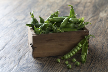 Green sweet peas in wooden box on brown wood surface