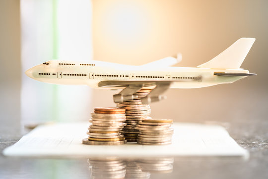 Saving and Travel Concept. Toy airplane model on stack of coins and book bank.