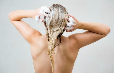 Woman washing her blond hair with shampoo