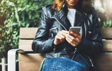 Fotomurales - Girl in leather jacket holding smart phone on bench background sun atmospheric city, hipster using in female hands and texting mobile, street lifestyle, tourist planing route in summer concept