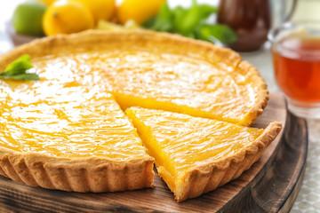 Yummy lemon tart on wooden tray
