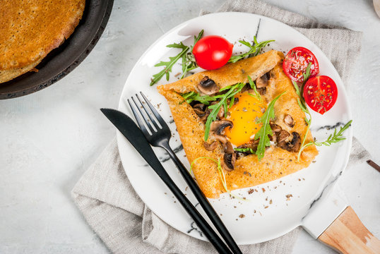 French cuisine. Breakfast, lunch, snacks. Vegan food. Traditional dish galette sarrasin. Crepes with eggs, cheese, fried mushrooms, arugula leaves and tomatoes. On white table. Copy space top view