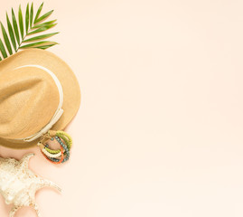 Summer fashion, summer outfit on cream background. Seashell, wood bracelet and straw hat. Flat lay, top view.