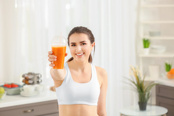 Beautiful young woman with cup of juice at home. Diet concept