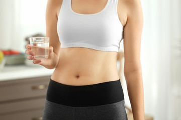 Beautiful young woman with glass of water at home, closeup. Diet concept