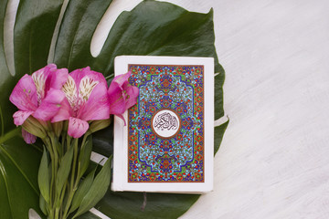 holy Quran on white wooden background with beatiful flower