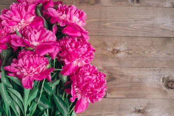 Row of peonies on wooden background with space for message. Women's or Mother's Day background. Top view