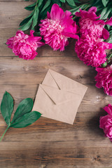 Row of peonies and paper card and on wooden background with space for message. Women's or Mother's Day background. Top view