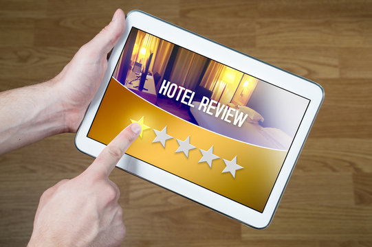 Bad hotel review. Disappointed and dissatisfied customer giving terrible rating with tablet on an imaginary criticism site, application or website. One out of five stars to accommodation or lodging.