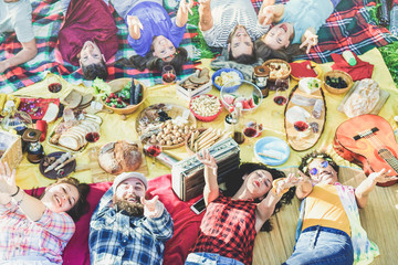 Top view of happy friends at picnic on city park outdoor - Young having fun at bbq dinner in summer time - Focus on bottom guys hands  - Food , vacation and friendship concept - Warm retro filter