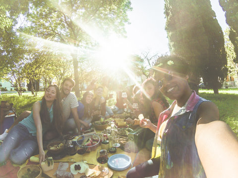 Happy mixed race woman taking selfie at picnic outdoor with her friends - Young trendy people having fun while eating and toasting red wine - Youth concept