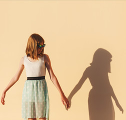 the girl holds the hand of her shadow