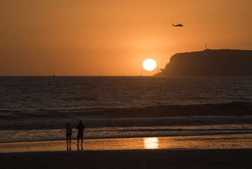 Couple watching dramatic orange and yellow sunset on Coronado island in San Diego California with helicopter