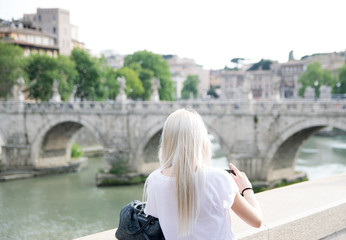 A blonde woman, seen from behind, is taking a photo of Castel St'Angelo in Rome on a summer day