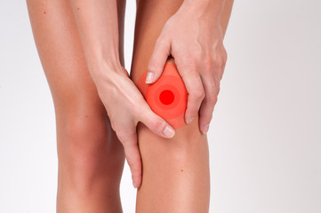 Close-up of female hands touching leg, feeling pain in knee.
