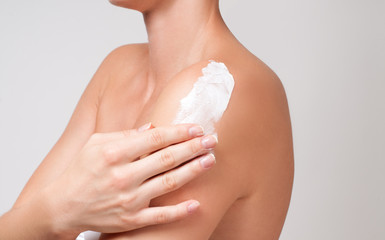 Body care. Woman cares about her shoulder applying cosmetic cream