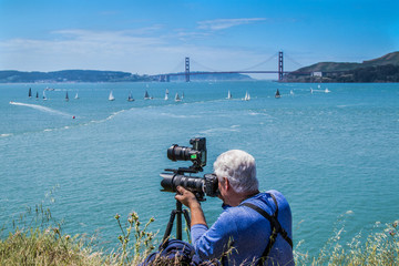 A male photographer using two cameras takes pictures on Angel Island across the San Francisco Bay from the landmark Golden Gate Bridge