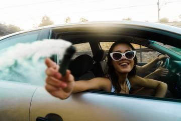 Smiling woman in car window posing