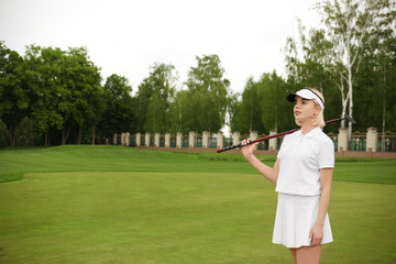 Beautiful young woman on golf course in summer day