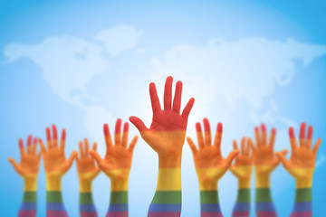 Rainbow multi-color flag pattern on many people's hands isolated on blue sky world map (clipping path)