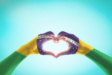 Photo sur Toile Brésil Brazil flag on people hands in heart shape for labor day and national holiday celebration isolated on blue sky background