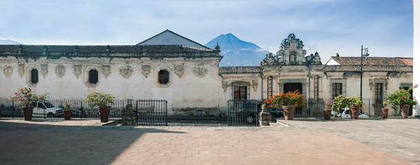 Side Street Facade of the Museum of Colonial Arts, one of the Heritage Buildings in Antigua, Guatemala with Agua Volcano in the background, surrounded by a few clouds as per usual.
