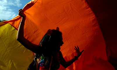 A participant dances under a rainbow flag during the annual Gay Pride parade in Managua