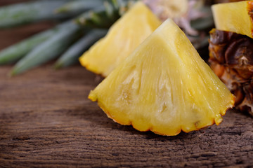 portion cut ripe pineapple on wooden table