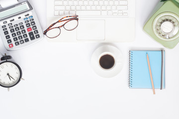 Flat lay of workspace desk with white laptop, stationery and cup of coffee