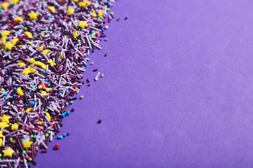 Colorful sprinkles on the purple background