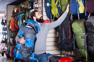 Young guy choosing new backpack in  shop