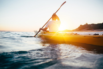 Kayaking at sunset sea