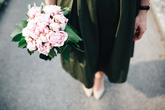 Low section of woman holding bunch of peony flowers