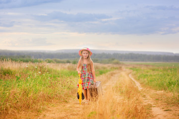 A sweet girl with a suitcase and an umbrella is walking along the field