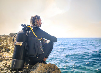 Scuba diver sitting on a rock, looking the sea Wall mural