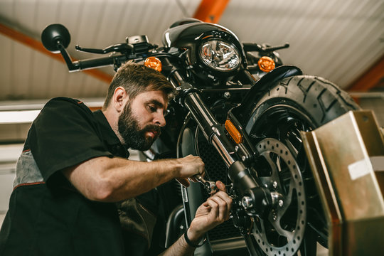 A professional mechanic unscrews the front wheel of a motorcycle. Bike is on the lift at the service station.