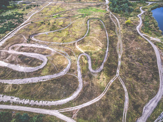 rolled tracks in countryside terrain with grove, top view, aerial photo