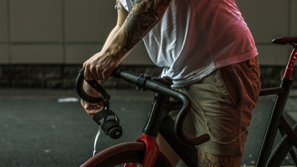 Foto op Plexiglas Tattooed biker hipster man in shorts winding the bar tape on a fixed gear bike handlebar