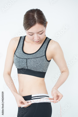 c59f650c40 Healthy fit and firm Asian woman measuring her waist looking at measuring  tape