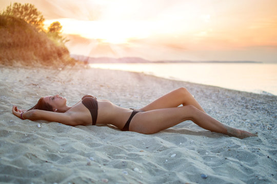 Seductive young woman in sexy black swimsuit laying on the sand at the beach during sunset.